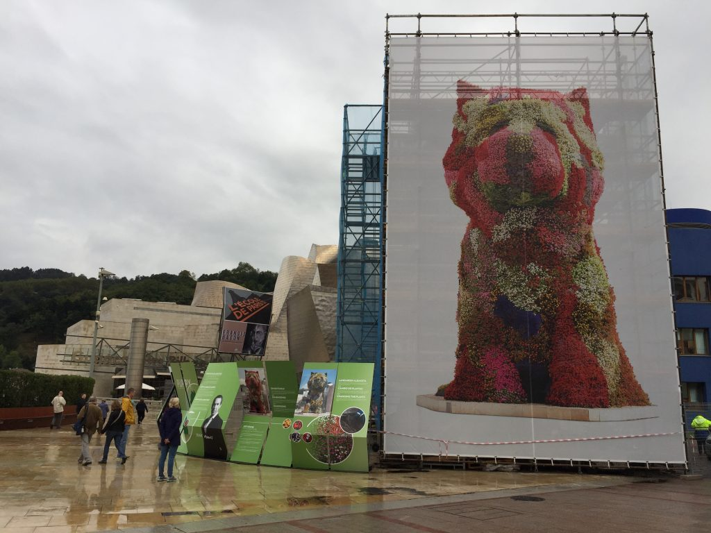 "Jeff Koons' ""Puppy"" at the Guggenheim entrance: 12.4 m high with 38,000 plants. Being re-vegetated when we visited."